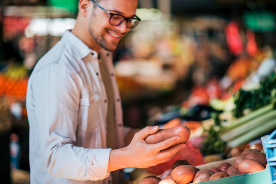 Close-up of a happy casual young man buying vegetables at local market.