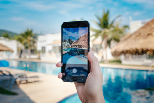 hand holding phone on background of the pool in hotel. photo camera on the screen.