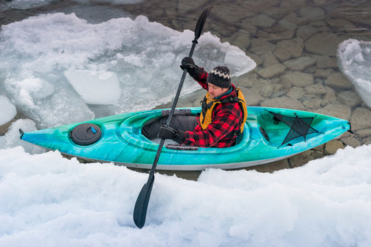 Man navigates icy water on winter kayaking adventure