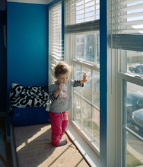Toddler sucking on a fruit pouch and griming up the windows