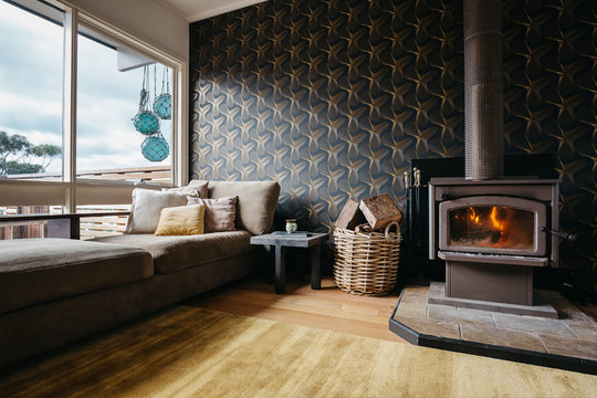 Cosy living room with large windows and a burning fire