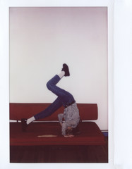 Casual girl making handstand on sofa