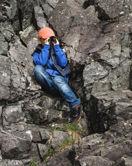 Young boy surveying the rocky seashore with a small binocular.
