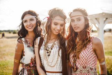 Three cute beautiful hippie girl in the setting sun, outdoors, the best of friends smiling and having fun, makeup, long hair, feathers in their hair, bracelets, flash tattoo, indie, Bohemia boho style