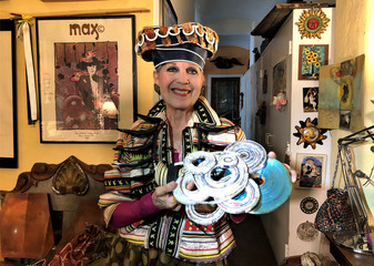 Artist Debra Rapoport, known for her wearable art since the late 1960's, poses with a hat she made out of newspaper at her home in New York City