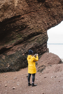 A Young Female Takes Photos Of Large Rocks