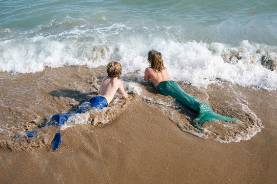 Two little girls with mermaid swimwear at the seashore