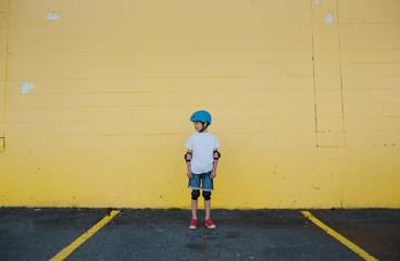 Kid wearing bike gear and helmet.