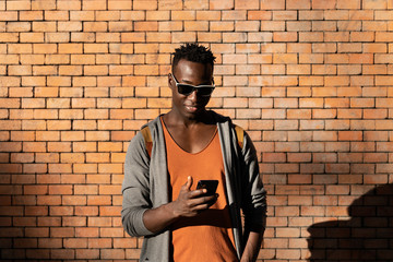 Portrait of young african american man using the mobile phone