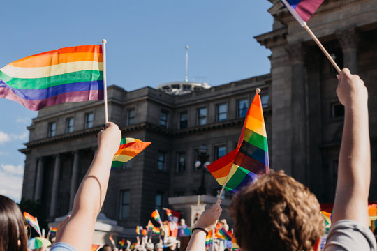 Crowd of people waving rainbow flags at pride parade