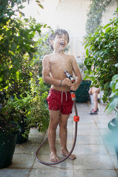 7 year old son playing with water outdoor