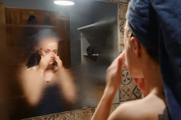 Woman touching face and looking at mirror