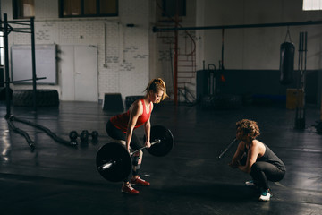 Blond young woman lifting a barbell in gym