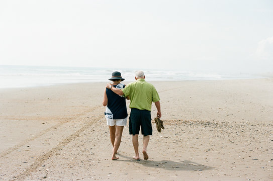 Older couple walking together on a beach