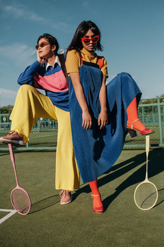 Hipster girls in badminton court posing with foot on racket