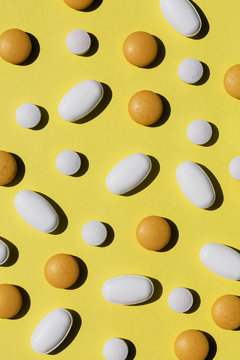Scattered vitamins on a lemon yellow background