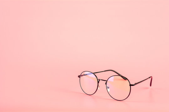 Eyeglasses on pink background.
