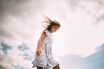 Little girl in dress dancing in the sunset with wind blowing hair