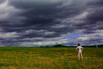 Boy looking at clouds and an empty field