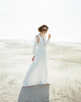 Smiling bride walking on sand