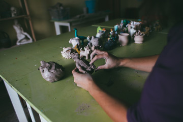Mid section of female potter molding a clay in pottery shop