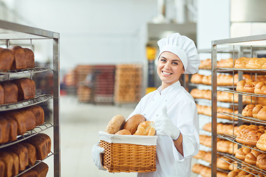 A baker woman holding a basket of baked in her hands at the bakery