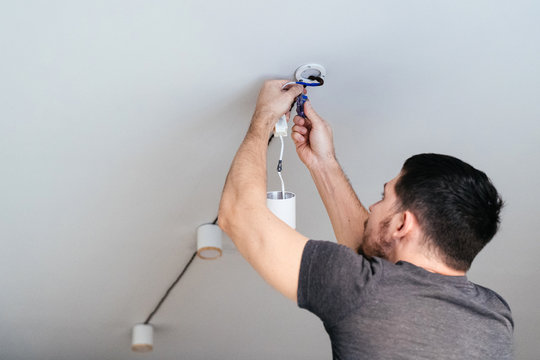 The man in his house fixes the lamp to the ceiling with a screwdriver.