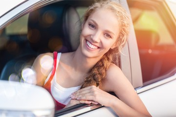 Portrait of Smiling Young Woman Looking out of the Window of her Car