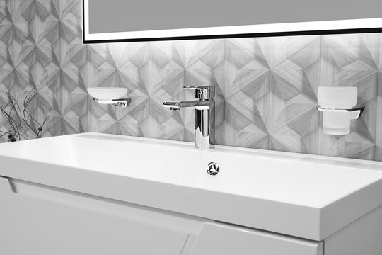 Luxury modern style faucet mixer on a white sink in a beautiful gray and white bathroom