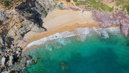 Aerial drone bird's eye view of famous emerald sea rocky beach of KAPE in area of Legrena, Sounio, Attica, Greece