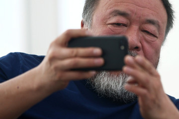 """Chinese artist Ai Weiwei takes photos during a news conference for his exhibition """"Restablecer Memorias"""" displayed at MUAC in Mexico City"""