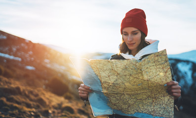 Wall Mural - traveler girl hold in hans map and look sun flare, people planning trip, hipster tourist on background nature, enjoy journey landscape vacation trip, lifestyle holiday concept, sun mountain