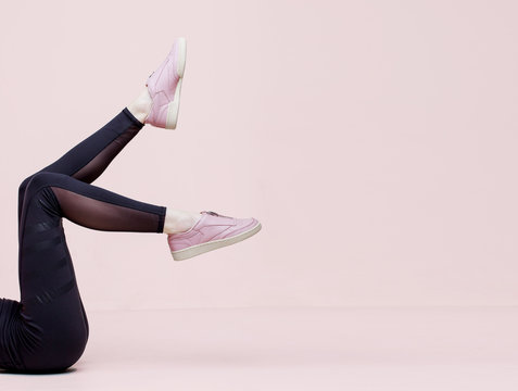 Stylish female shoes in pastel colors. Flat lay. Beautiful woman legs in pink sneakers and black leggings on peach background. Beauty, fashion, trendy sportswear, minimal idea creative concept.