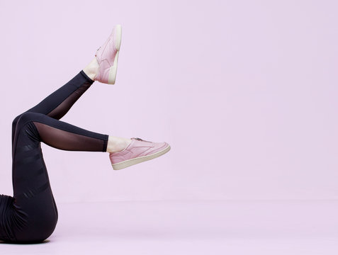 Stylish female shoes in pastel colors. Flat lay. Beautiful woman legs in pink sneakers and black leggings on pink background. Beauty, fashion, trendy sportswear, minimal idea creative concept.