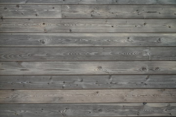Flat gray brown wood surface with aged boards lined up. Wood paneling with grain and texture.