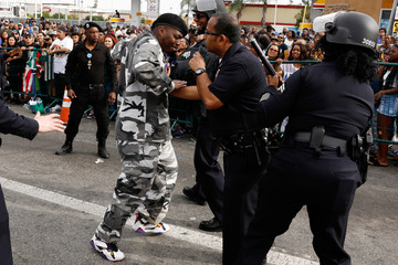 A man confronts LAPD officers after fans filled the streets while waiting for the funeral procession for rapper Nipsey Hussle in Los Angeles