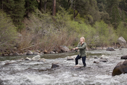 A young woman fly fishing in a fast moving river in the Sierra Nevada Mountains in Northern California.
