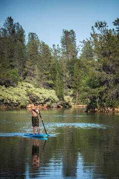 A an active boy paddling a paddle board on Whiskeytown Reservoir in the Sierra Nevada Mountains of Northern California on a warm summer day.