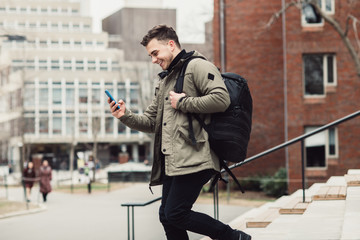 Happy student man text on cell phone walking in city college campus with backpack