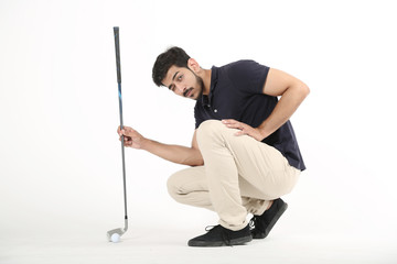 Picture of handsome boy sitting with golf stick and golf ball. Isolated on white background.