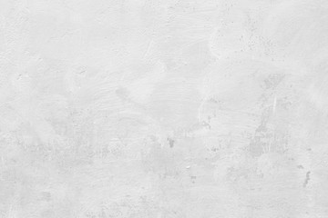 Close-up of a stone or concrete wall painted in white, paint slightly peeled off. Full frame texture background in black and white.