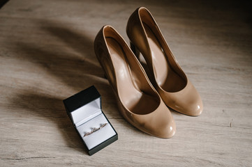 Wedding accessory bride. Stylish lacquered beige shoes, earrings, gold rings are isolated on table...