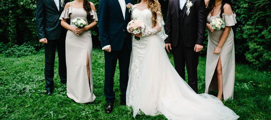 Newlyweds with groomsmen and bridesmaids having fun outdoors. Bride and girls with bouquets of flowers and groom with boys friends are standing together in nature.