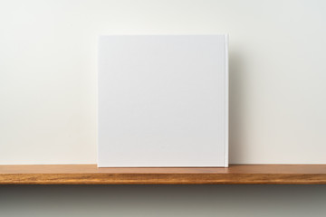 white square notebook on bookshelf and white wall