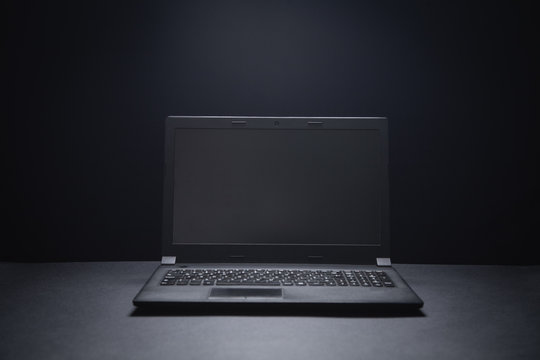 Black laptop on the black office desk. Technology concept