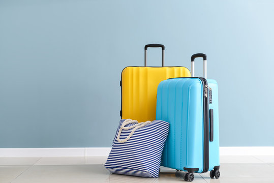Packed suitcases and beach bag near color wall