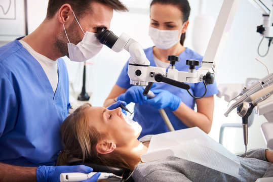 Male dentist working with dental microscope