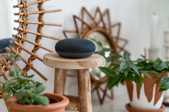 VIENNA,AUSTRIA - April 4 : Google Home Mini on a wooden table with green plants in the background