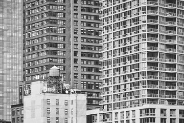 Black and white picture of a water tower on a rooftop, New York City, USA.