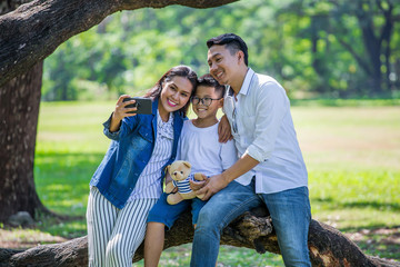 happy asian Family, parents and their children taking selfie in park together. father, mother ,son sitting on branch of big tree take a photo by smart phone having fun and laughing outside .cheerful